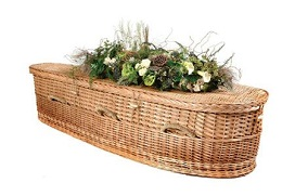 basket weave casket with flowers on top and woven handles